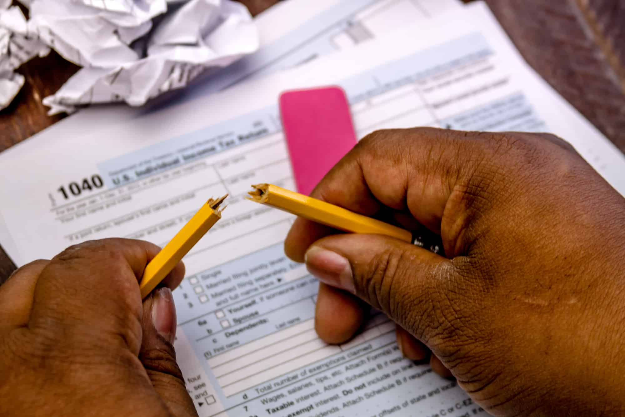 Black male hands holding broken pencil with tax form 1040 for bartering income