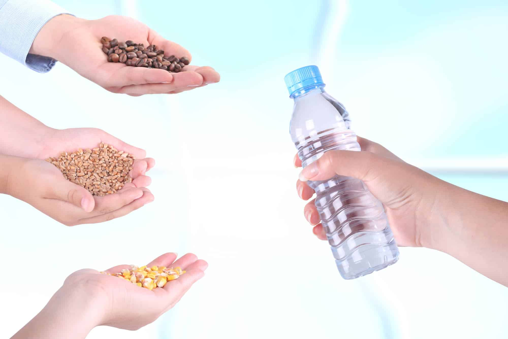 People's hands offering to barter corn, grains and coffee for bottled water in a barter network.