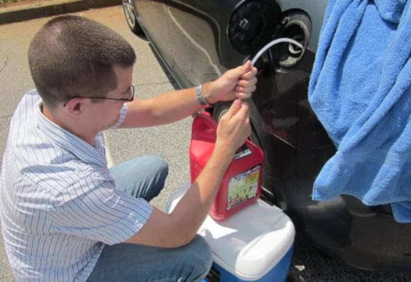 Caucasian man with buzzed hair siphoning gas from a car into a canister