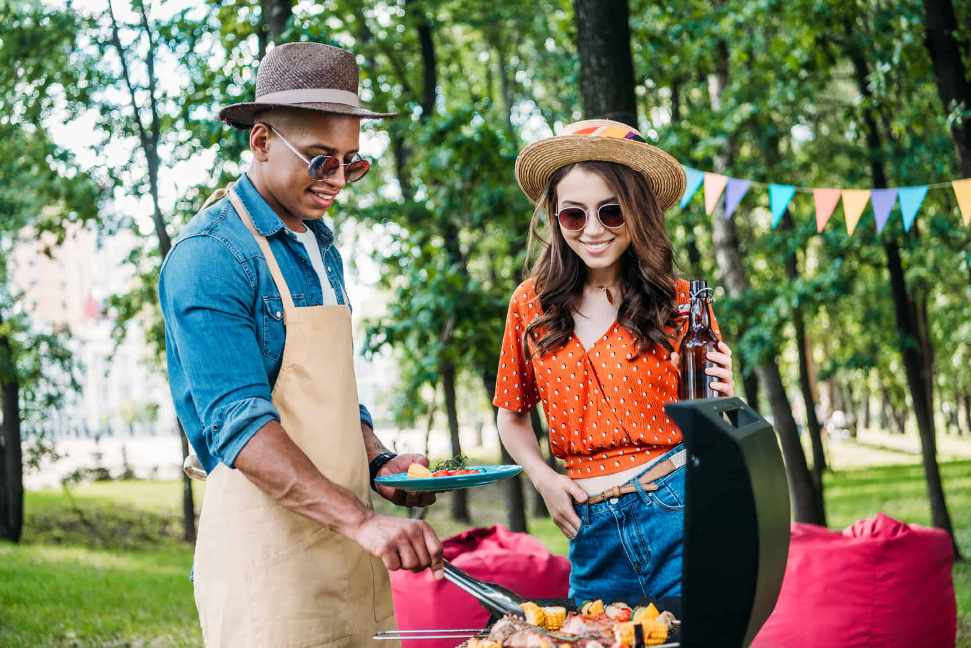 Happy smiling couple grilling in a park thinking about being a business owner as a chef