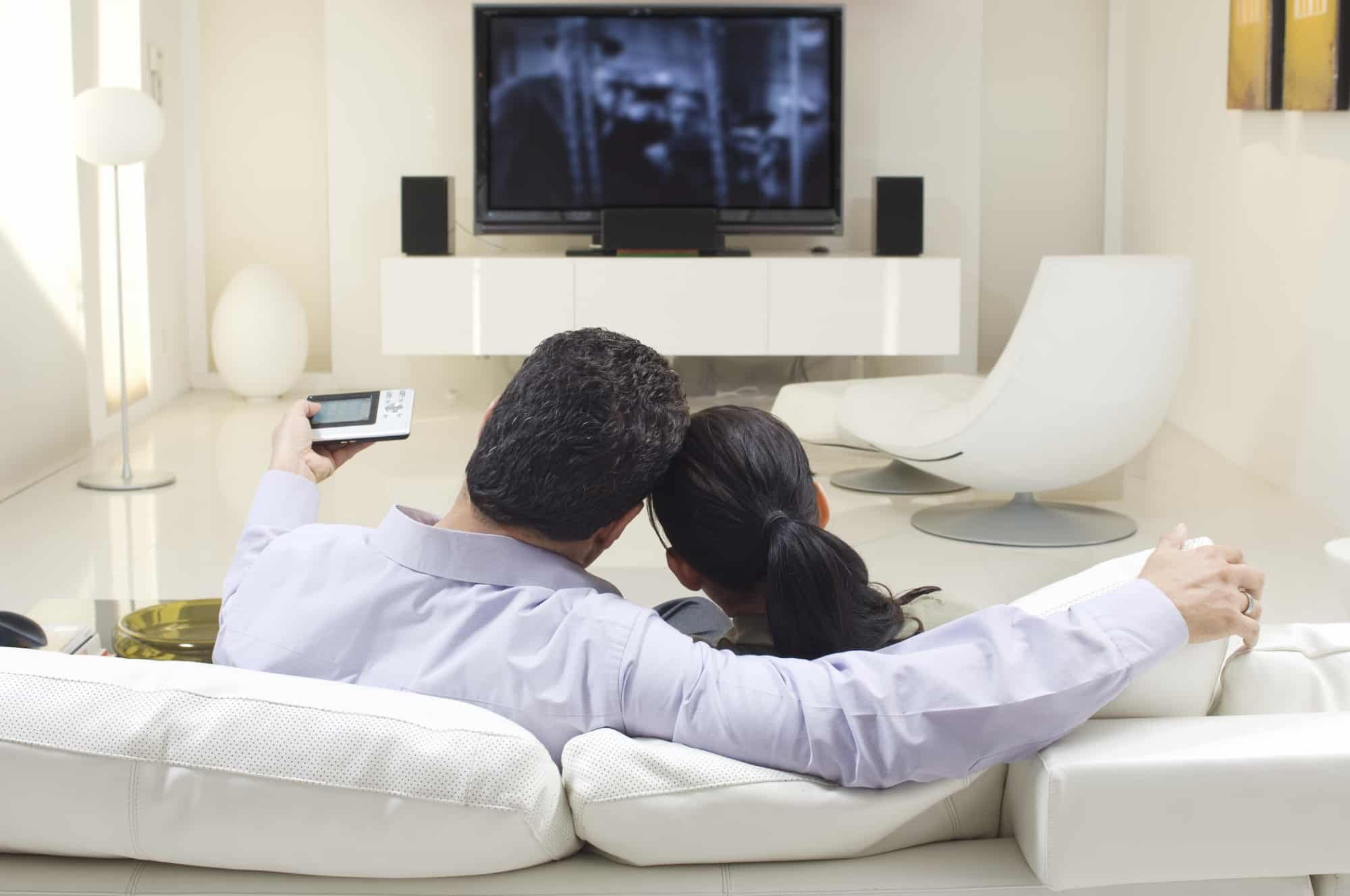 Couple watching cable television on a high-definition TV with surround sound speakers, cuddling on a white leather couch.