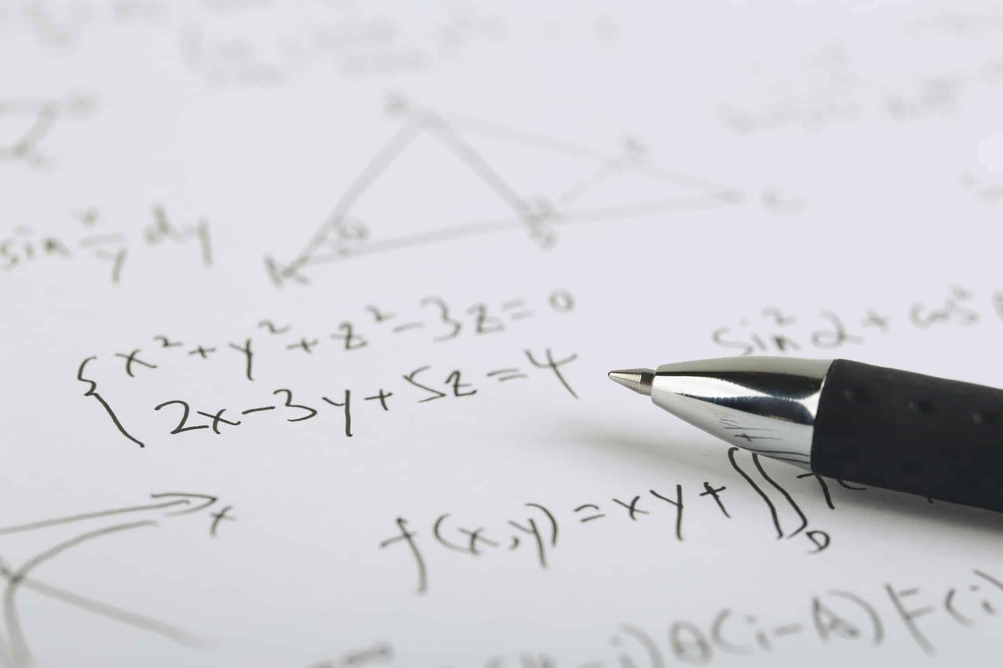 Calculating net income using complex math formulas on paper with a black ceramic ball pen.