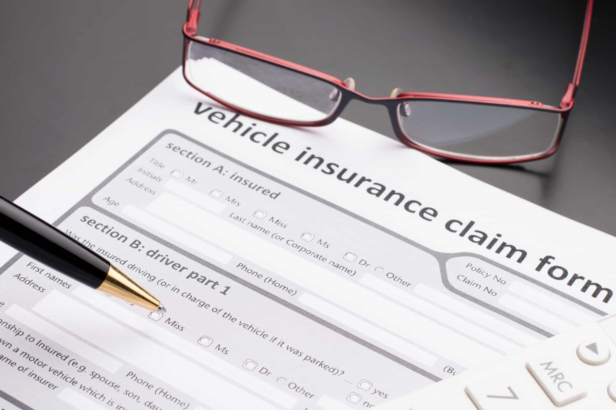 Car insurance claim form with a black lacquer ballpoint pen and red reading glasses.