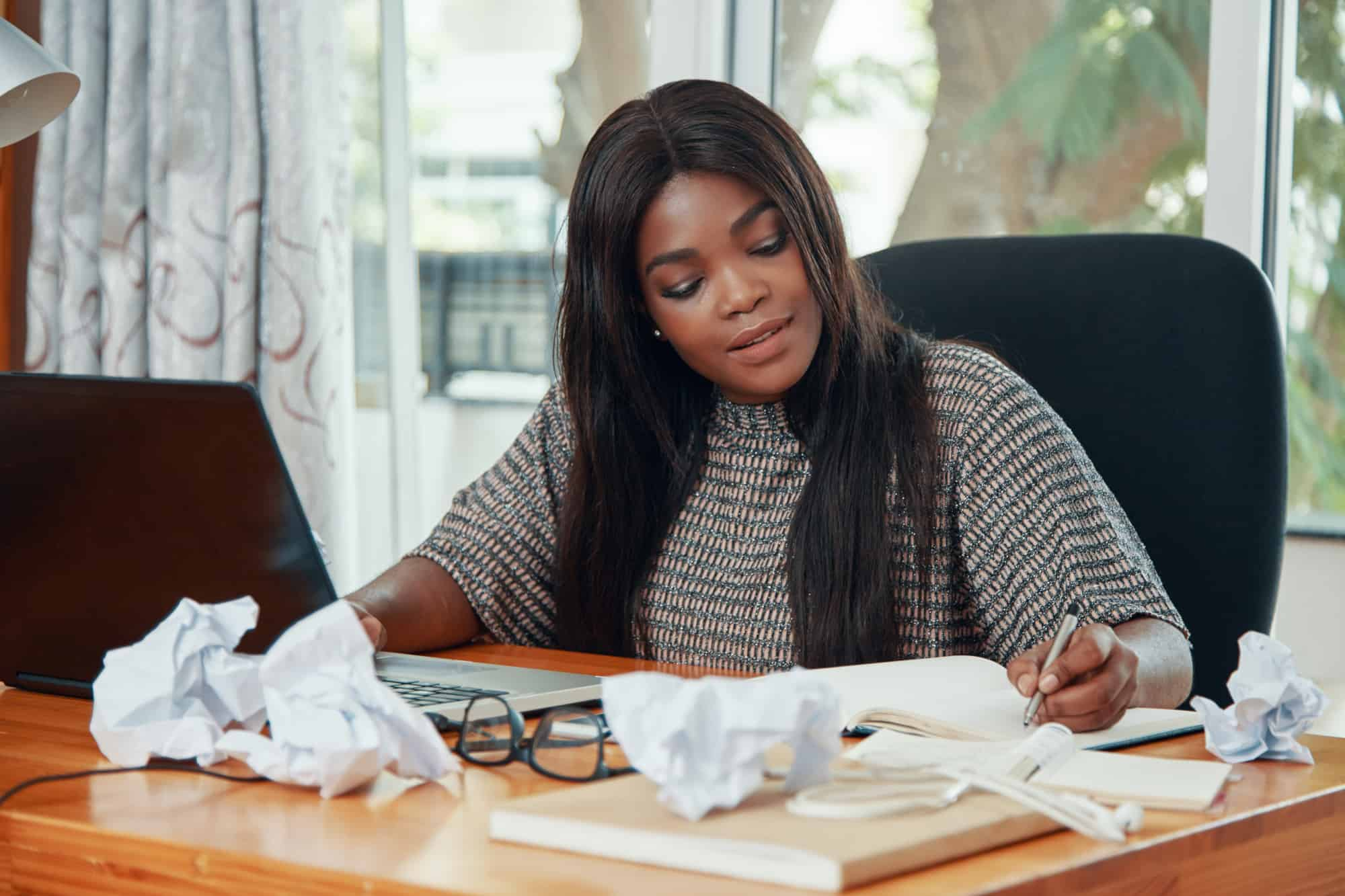 Black female digital nomad working on a computer with crumpled-up papers.