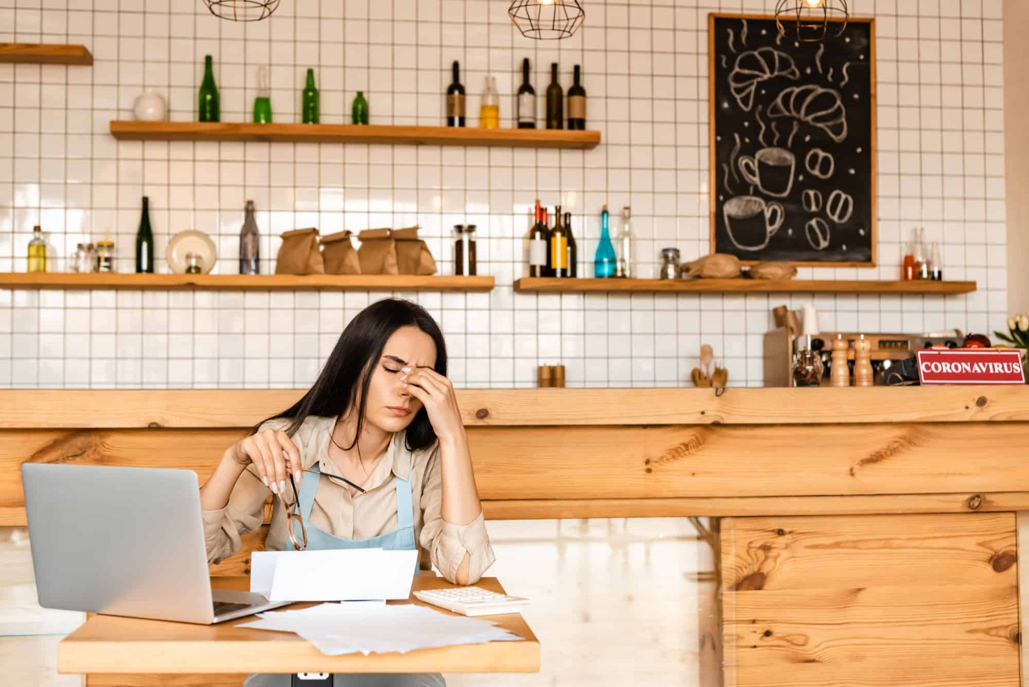 Exhausted female business owner doing closing work for her café.