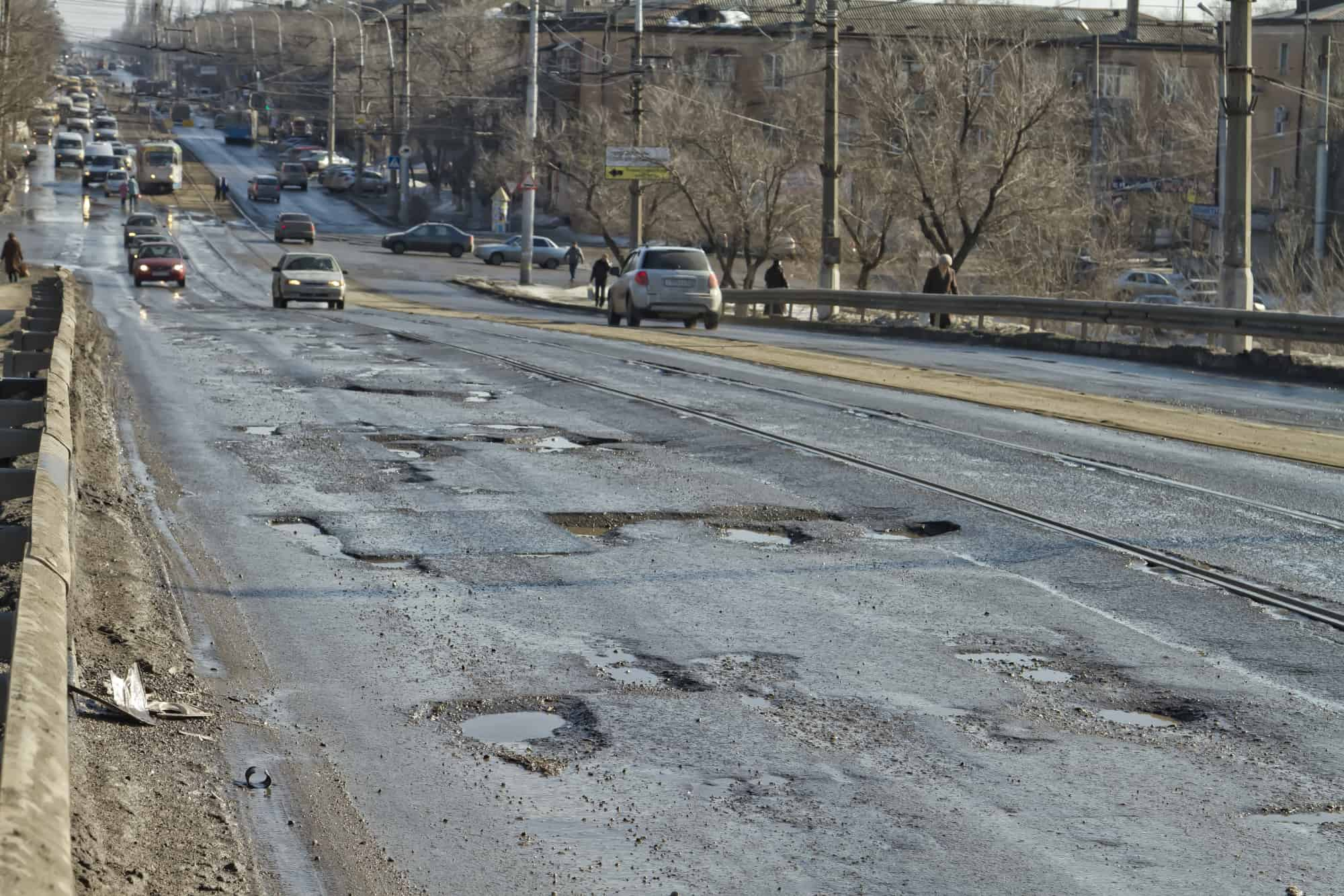 Stretch of uneven road with multiple potholes