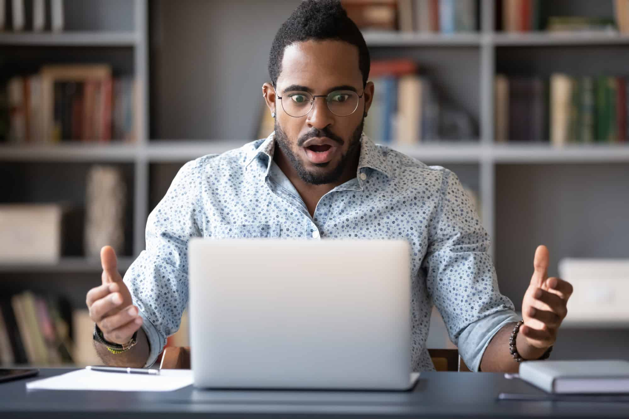 Black male surprised trying to figure out Instacart prices for grocery delivery service on a laptop