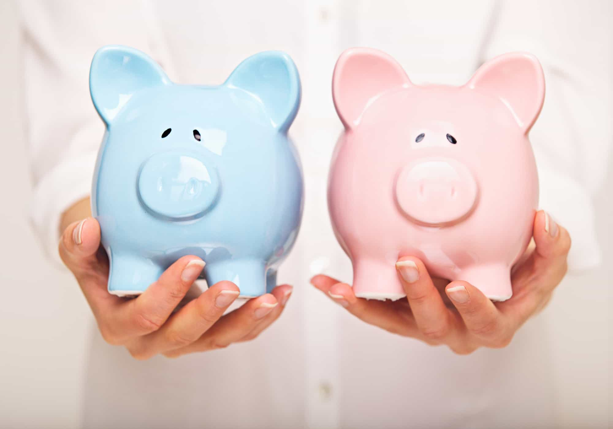 Pink ceramic piggy bank and powder blue ceramic piggy bank held in a woman's hands to separate bank accounts.