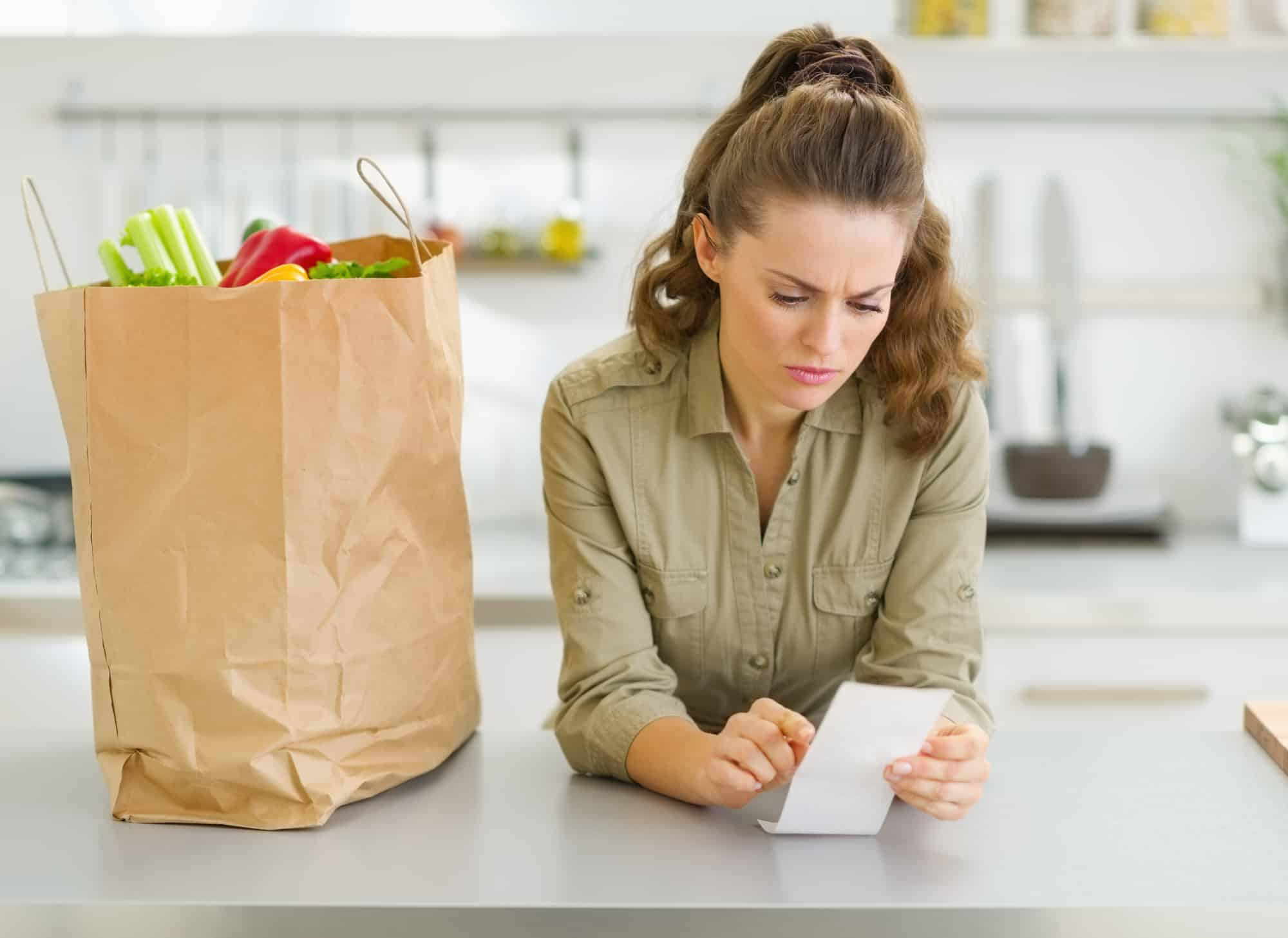 Woman looking over Instacart receipt with concern after receiving grocery delivery service order.
