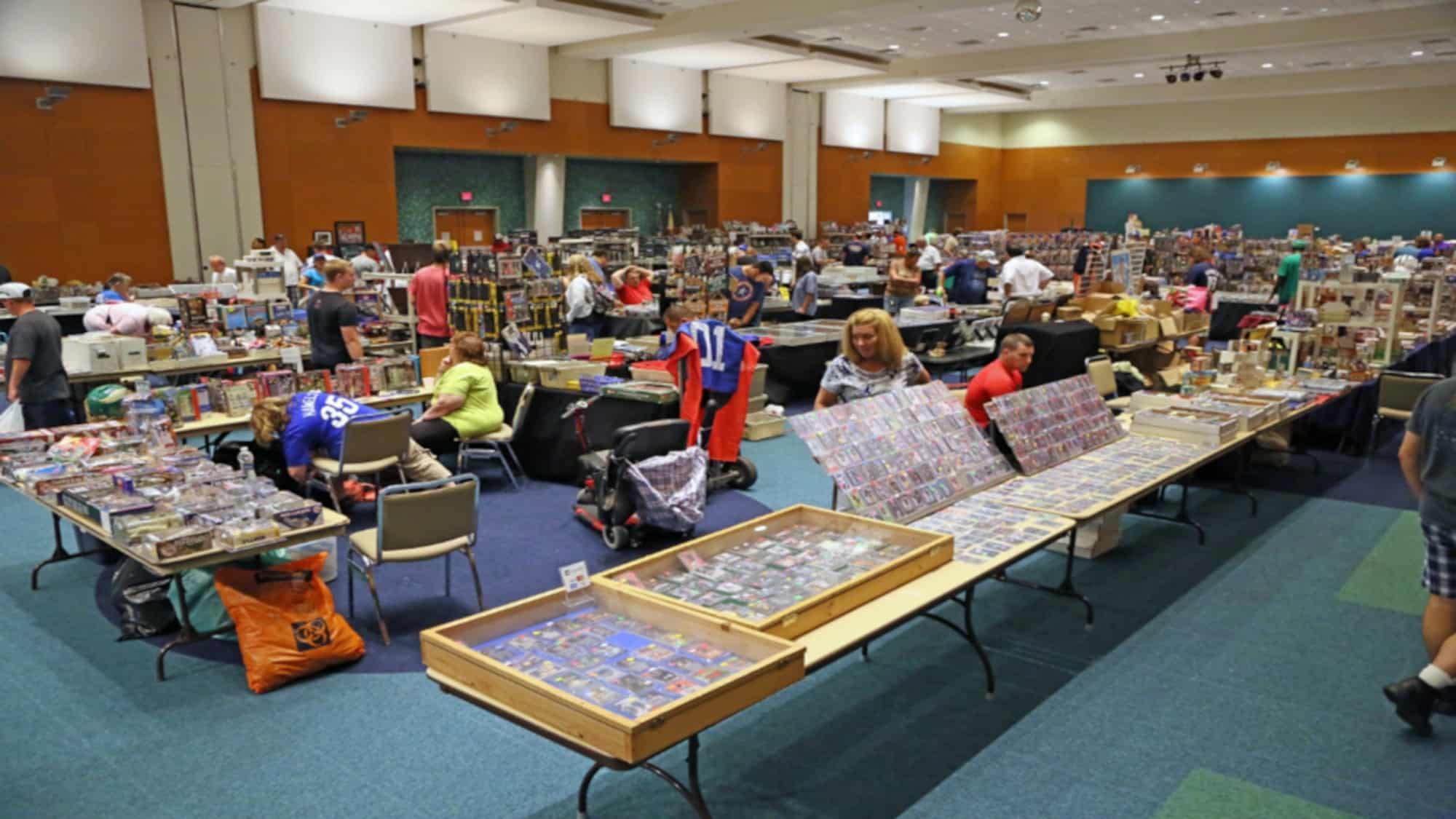 People investing in collectibles at a trade show buying and selling Pokemon cards, comic books, sports cards and more.