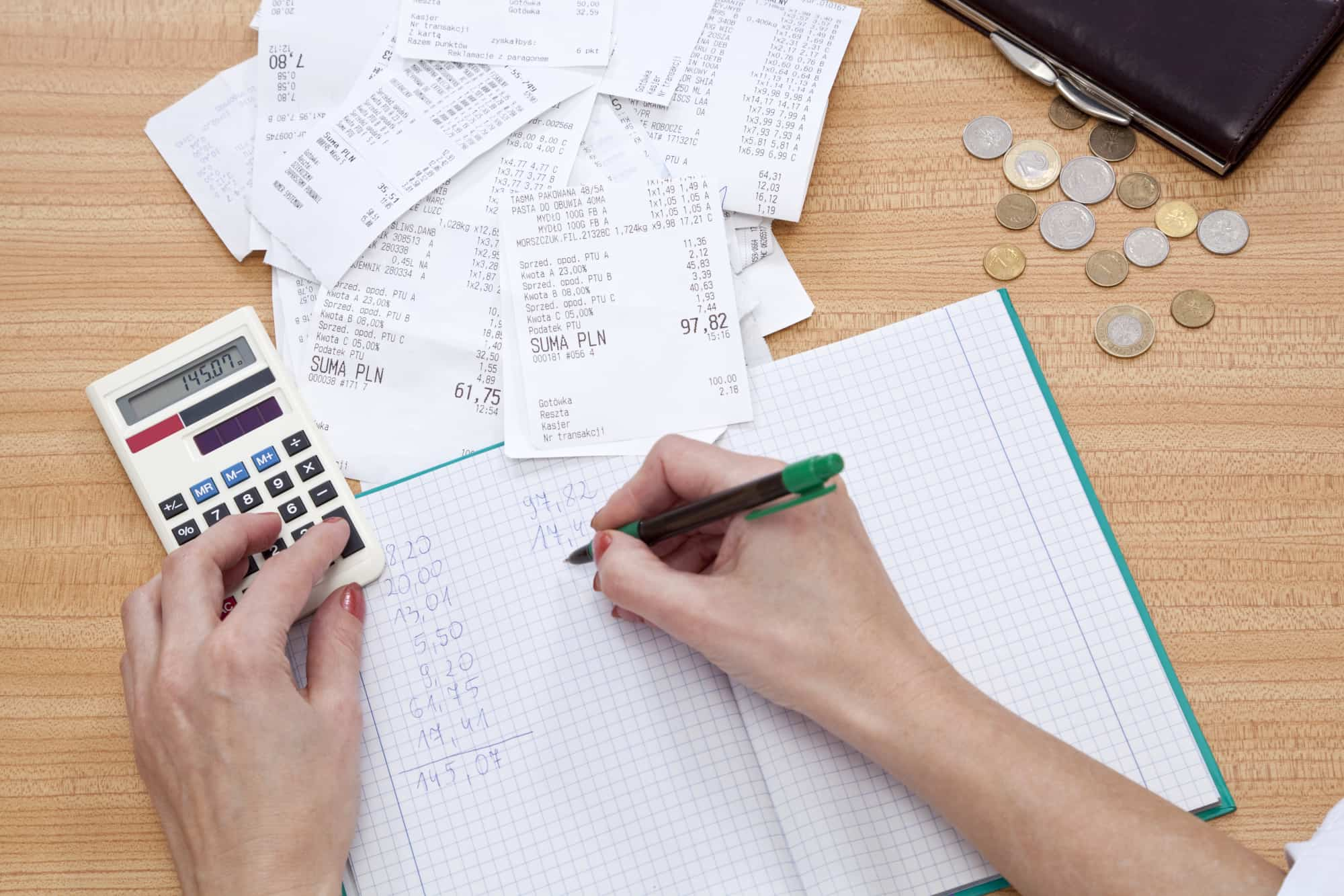 Woman calculating receipts to total all of the day's business expenses for recording.