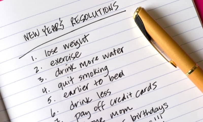 Lined paper in a notebook with a numbered list of New Years resolutions written in ink with a gold fountain pen