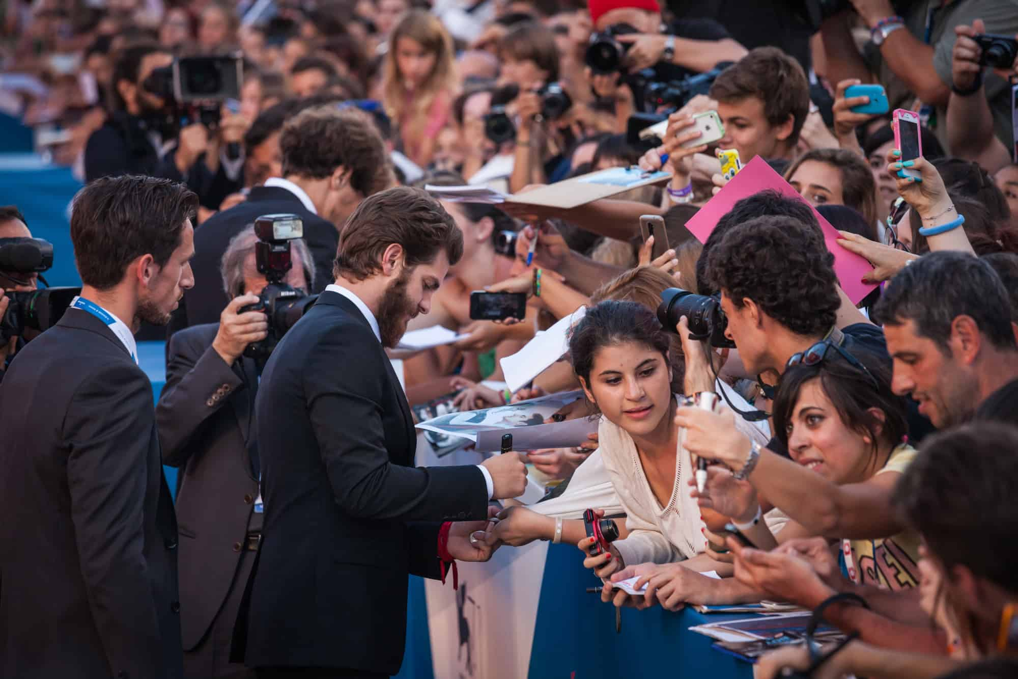 Actor Andrew Garfield signs autographs with fans at the '99 Homes' premiere during the 71st Venice Film Festival on August 29, 2014 in Venice, Italy