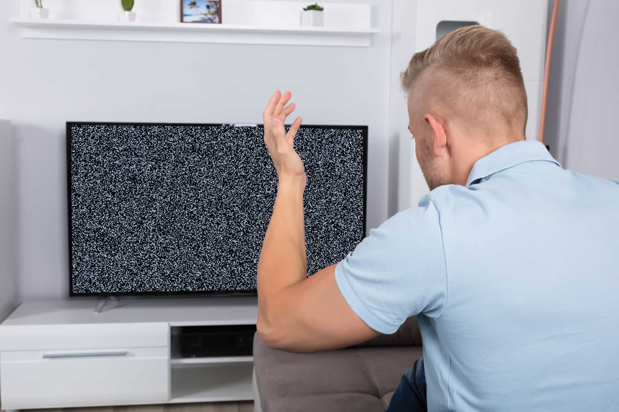 Blonde man wearing powder blue polo shirt getting no cable TV