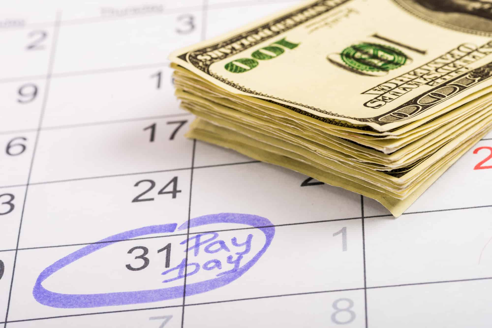 """Hundred dollar bills and the 31st on a calendar circled in purple marker with """"Pay Day"""" written as a reminder to pay yourself."""