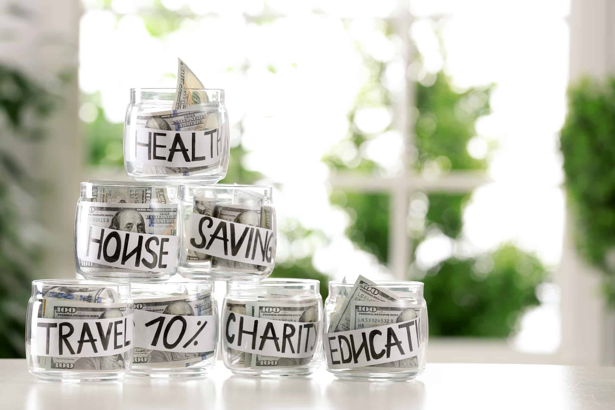 Jars of hundred dollar bills for savings goals and maintaining separate bank accounts.