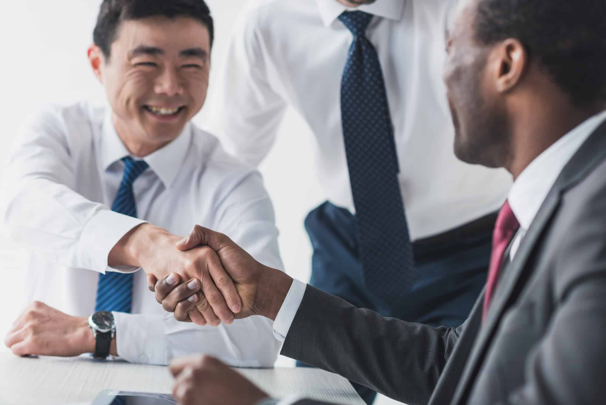 Black male tax accountant with a good personality laughing and shaking hands with East Asian male client