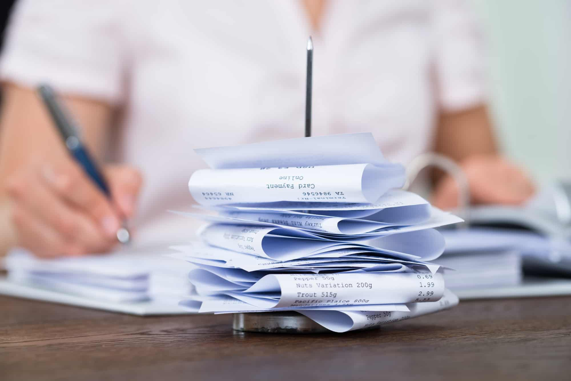 Female bookkeeper entering receipts into the ledger on a paper nail
