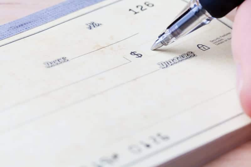 closeup of hand writing a personal check t a business that doesn't accept credit cards